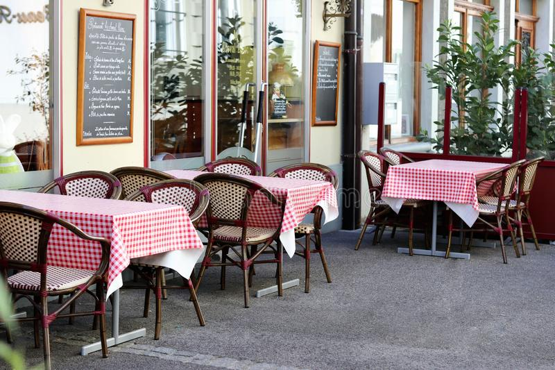 NYON, SWITZERLAND - APRIL 27, 2018: outdoor tables in cozy swiss restaurant in Nyon city stock photography