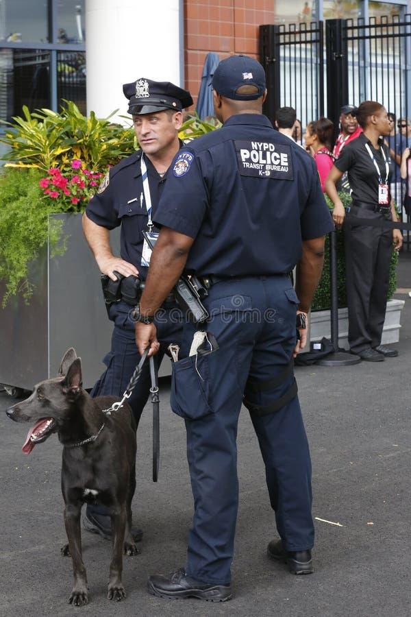 NYPD-doorgangsdienst k-9 politiemannen en Belgische Herder k-9 die SAM veiligheid verstrekken op Nationaal Tenniscentrum tijdens  stock foto's