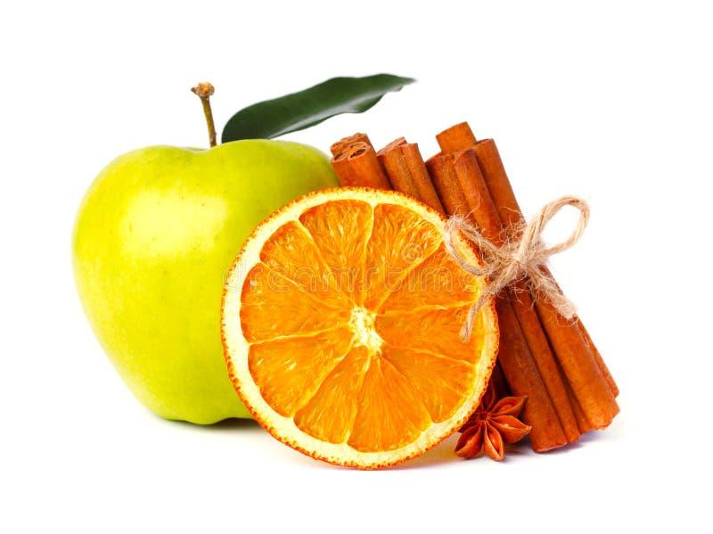 Nytt äpple, en skiva av den torra apelsinen och aromatiska kanelbruna pinnar, stjärnaanis som isoleras på vit royaltyfria foton