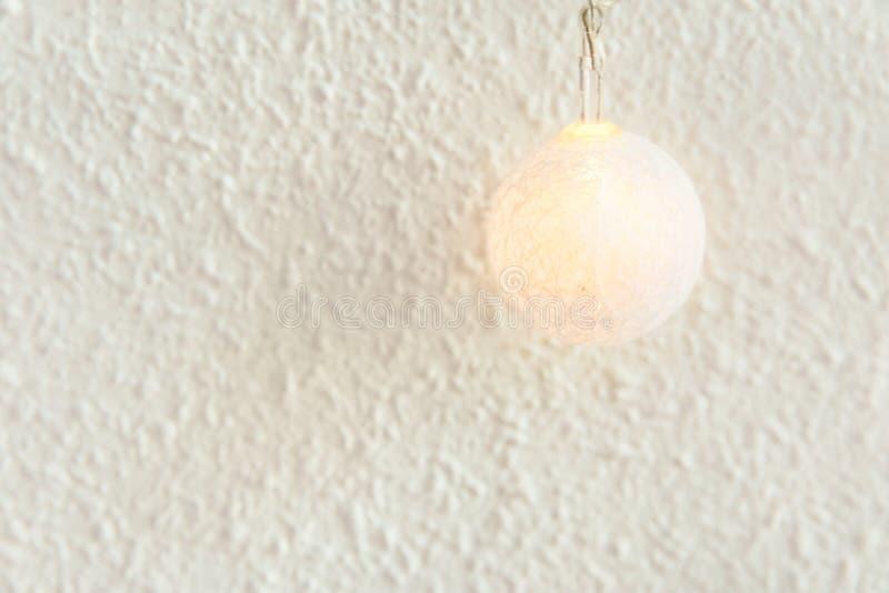 nytt år för bakgrundsjul Pastellfärgad guld- bomullsboll av girlanden på vit väggbakgrund Skandinavisk stil Glödande lampa arkivfoto