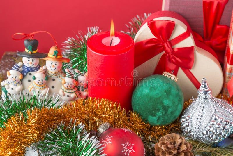nytt år för kortjul Rolig snögubbefamilj med att bränna den röda stearinljuset, kotten, giftboxes, bollar och paljetten mot röd b royaltyfria bilder