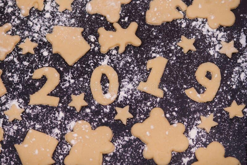 Nytt år 2019, förberedelse, kakor i form 2019 Rå deg för feriesötsaker arkivfoton