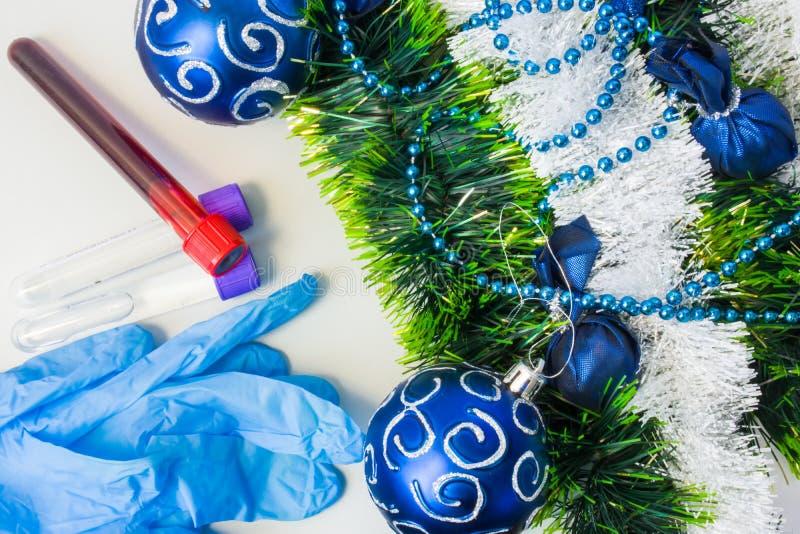 Nytt år och jul i klinisk eller vetenskaplig laboratoriumet det läkarundersökning, Skyddande handskar och laboratoriumprovrör med royaltyfri fotografi