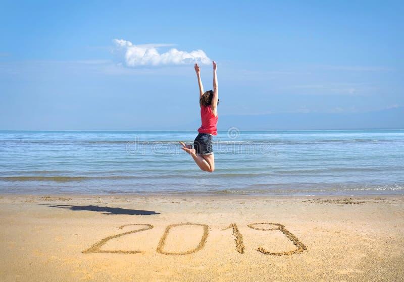 Nytt år 2019 på sanden, lycklig flicka med händer upp att hoppa på th fotografering för bildbyråer