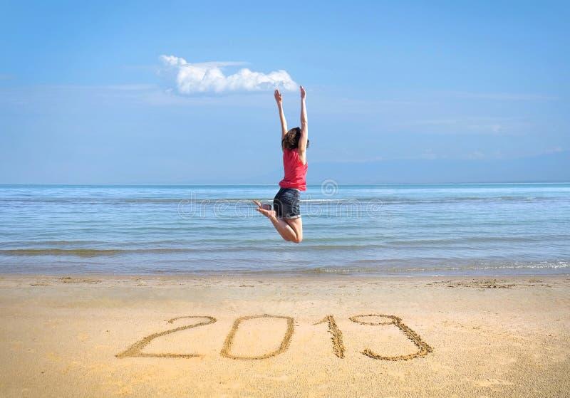 Nytt år 2019 på sanden, lycklig flicka med händer upp banhoppning på stranden arkivfoton