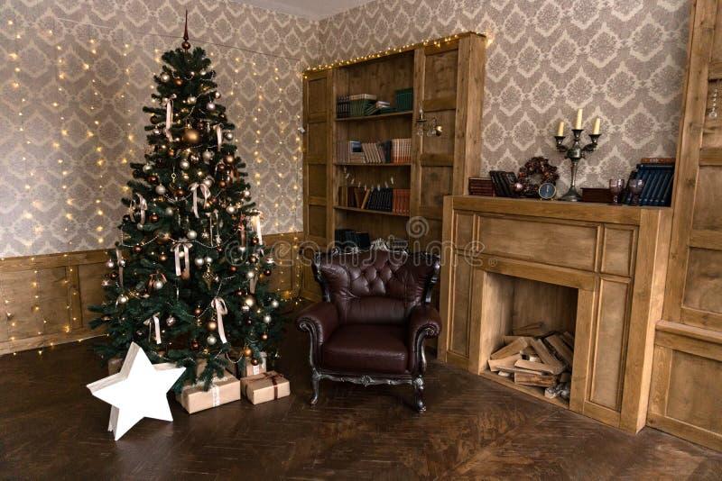 Nytt års dekor i rummet med en julgran, en spis och gåvor arkivbild