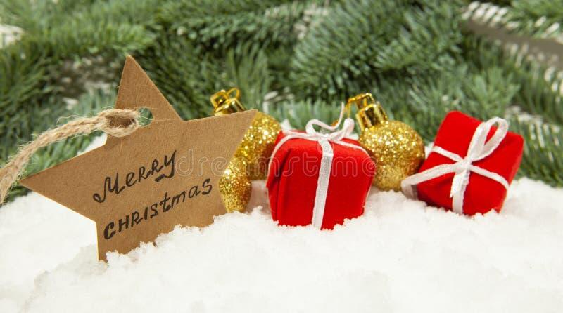 Nytt års dekor, julbollar och gåvor på vit snö royaltyfri foto