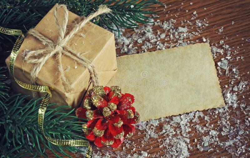 Nytt års gåva, de röda kottarna, granfilialerna och pappers- etikett royaltyfri fotografi