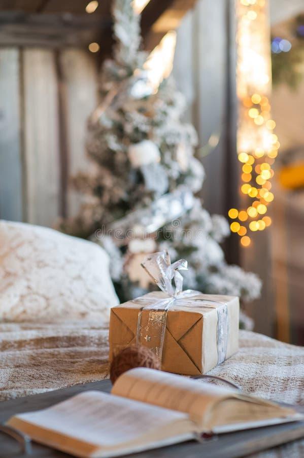 Nytt års gåva på sängen Skandinavisk sovruminre under jul Lantlig texturerad träsäng royaltyfri foto