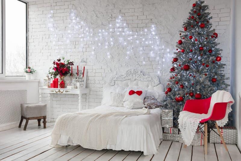 Nytt års inre, en vit fotostudio med en silverjulgran och en vit säng, röda julgrangarneringar royaltyfri bild