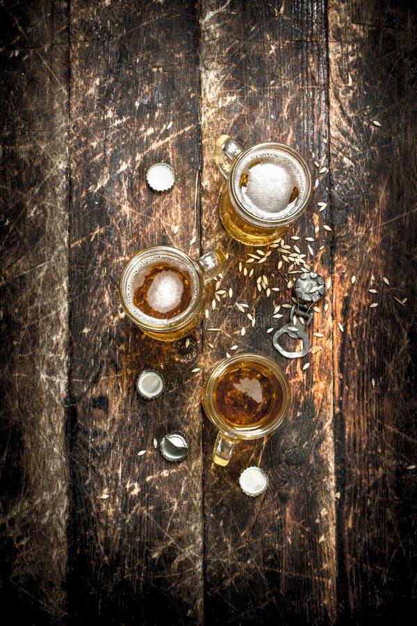 Nytt öl i ett exponeringsglas med proppar och en flasköppnare royaltyfri bild