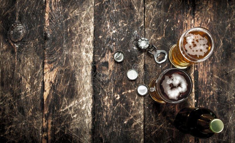 Nytt öl i ett exponeringsglas med proppar och en flasköppnare fotografering för bildbyråer