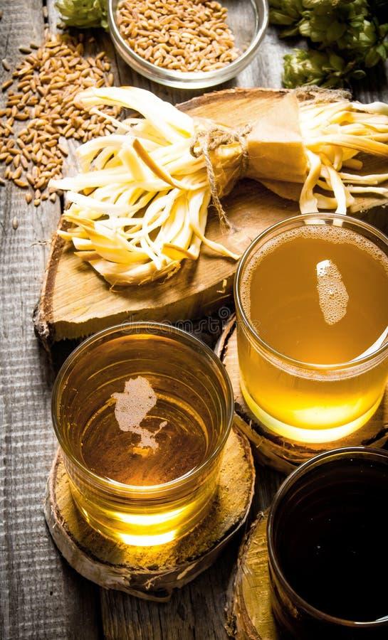 Nytt öl och den salta osten på en trätabell royaltyfria foton