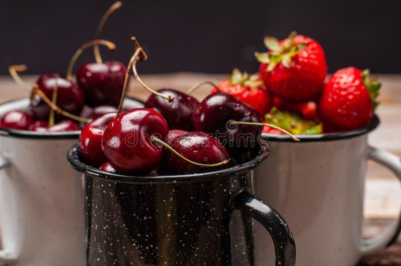 nytt bär Körsbär och jordgubbar i koppen på trätabellen royaltyfri bild