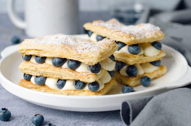 Nytt bakad Millefeuille kaka med smördeg, kräm och blåbäret arkivbilder