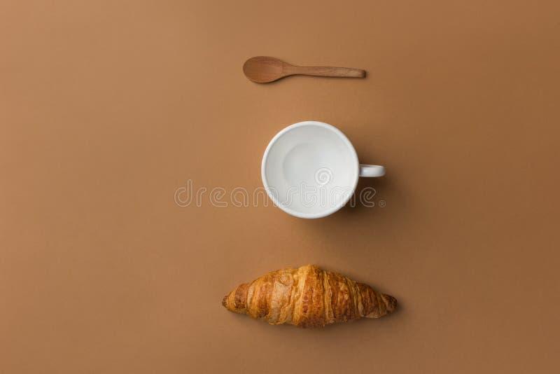 Nytt bakad tom kopp för fransk buttery flagig giffel för te- eller kaffeträsked på brun tabletop bakgrund Knolling arkivfoto