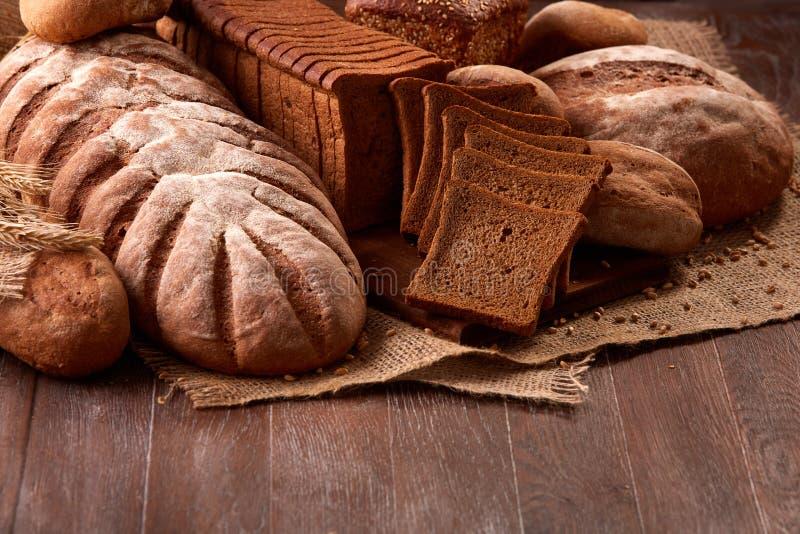 Nytt bakade brödloaves på säckväv på trätabellen med vete Produkter för texturcloseupbageri royaltyfri foto