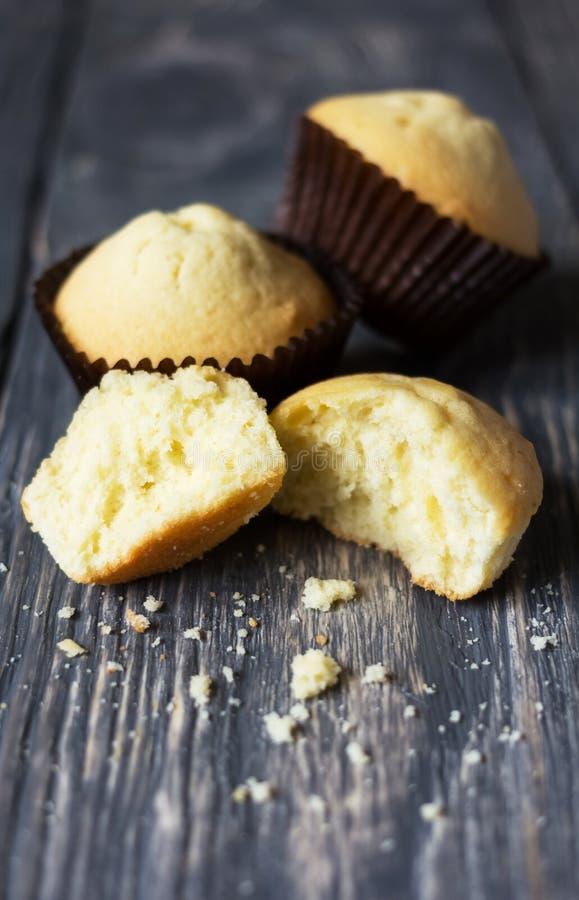 Nytt bakade muffin ligger på träyttersida, den nästa brutna muffin arkivfoto