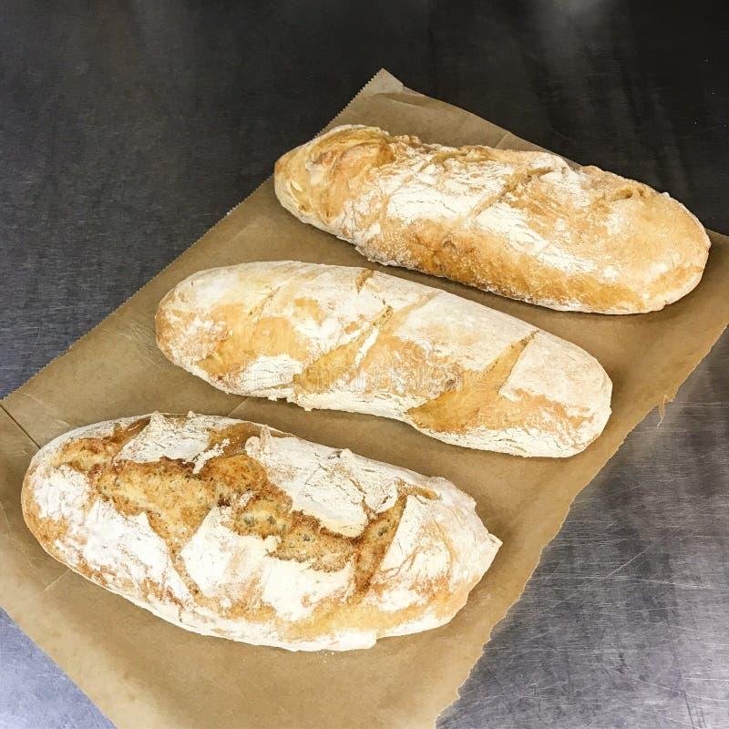 Nytt bakat bröd på papper arkivfoton