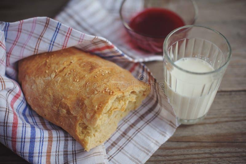 Nytt bakat bröd tjänade som med driftstopp, och exponeringsglas av mjölkar arkivfoto