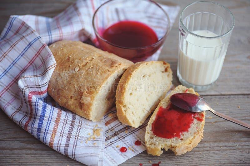 Nytt bakat bröd tjänade som med driftstopp, och exponeringsglas av mjölkar royaltyfri fotografi