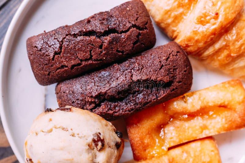 Nytt bakat gods på den vita maträtten inklusive sconesen, gifflet, finansiär och chokladfinansiär royaltyfri fotografi