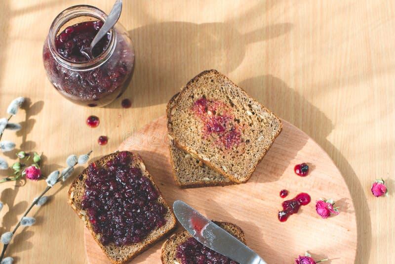 Nytt bakat hemlagat sunt bröd med svart vinbärdriftstopp - hemlagad marmelad med nya organiska frukter från trädgård I lantliga d arkivfoton
