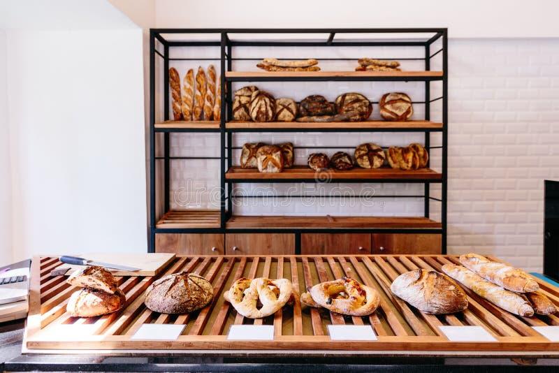 Nytt bakat mutter- och russinbröd, stavat bröd, baconfougasse, fougasse för körsbärsröda tomater för confit, nuage och bagett royaltyfria foton