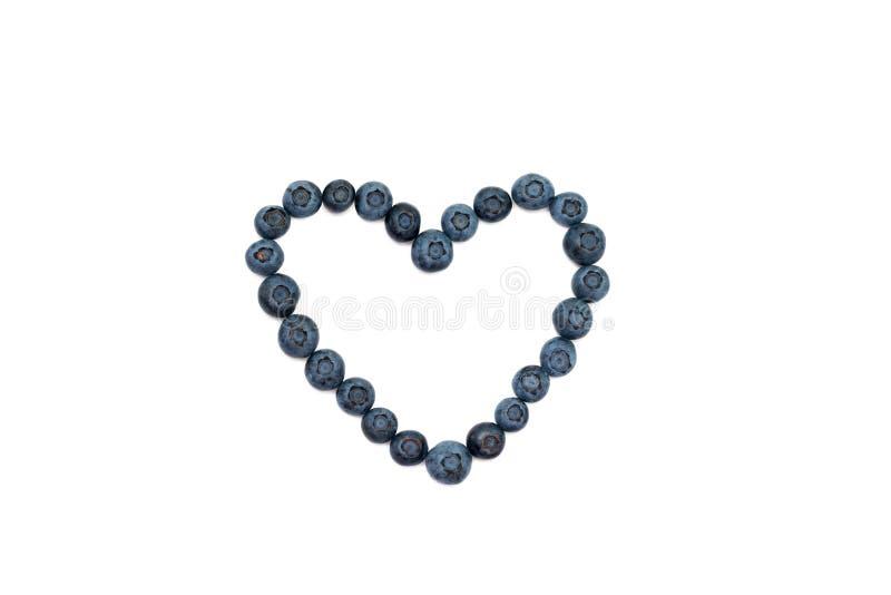 Nytt blåbär på vit bakgrund, hjärtaform royaltyfri bild