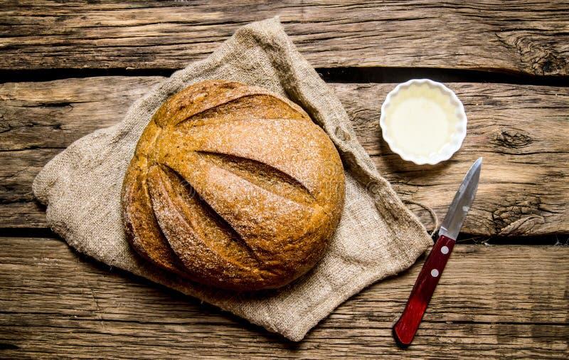 Nytt bröd med kniven och olja Top beskådar royaltyfri fotografi