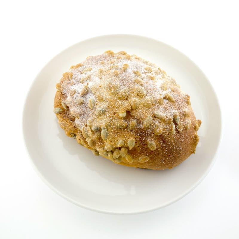 Nytt bröd med sojabönan och icezing toppning på vit plattaisolator royaltyfri bild
