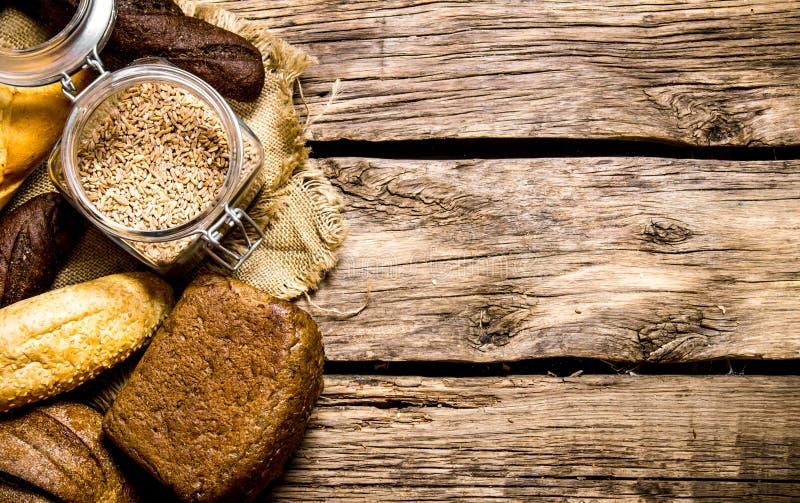 Nytt bröd med vetekorn trägrund tabell för djupfält arkivbild