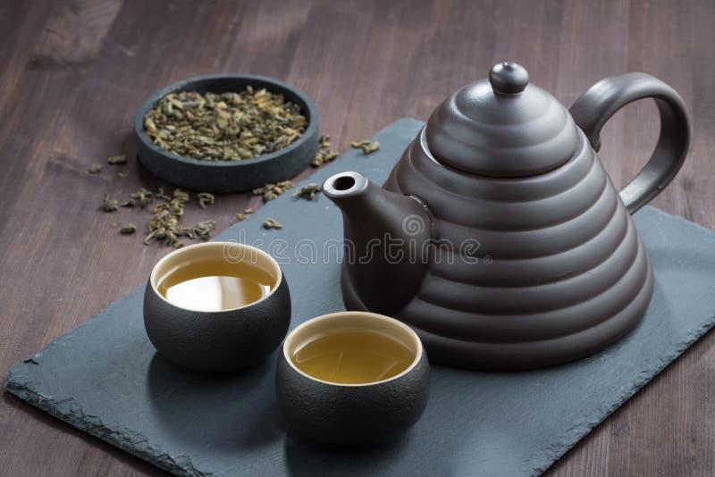Nytt bryggat grönt te i keramik på trätabellen arkivbild
