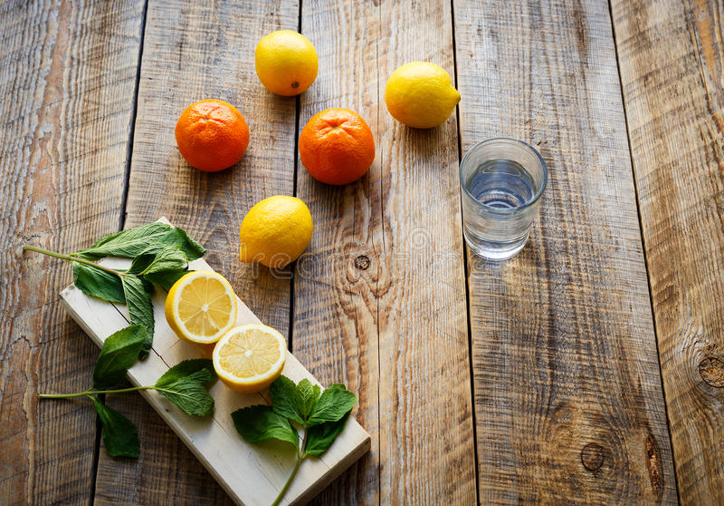 Nytt citroner och apelsiner med glass vatten på träbräden royaltyfria bilder