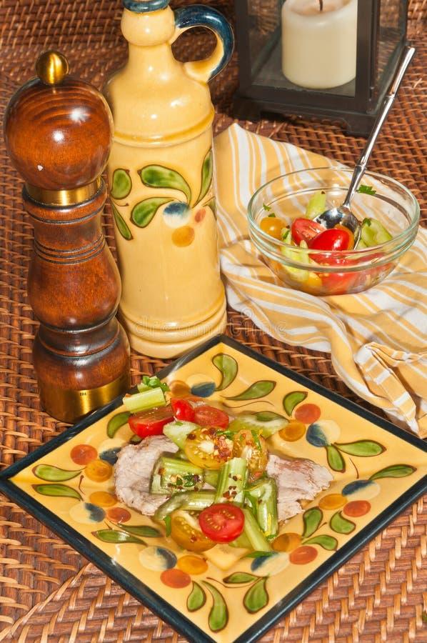 Nytt förberett, hemlagat, kalvköttscaloppine med selleri, halverade tomater med flingor för röd peppar arkivbild