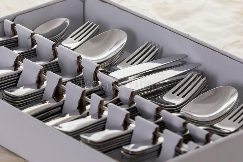 Nytt från lagret, skedarna, gafflarna, knivarna, kakagafflarna och teskedarna i en ask, på tabellen med den vita bordduken royaltyfria bilder
