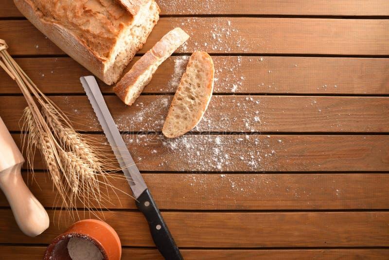 Nytt gjort klippte för att släntra av bröd på trätabellöverkant fotografering för bildbyråer