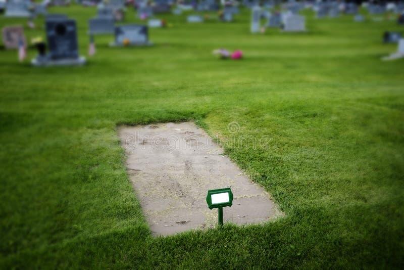 Nytt grävd grav i kyrkogård med gravstenar och grönt gräs royaltyfri fotografi