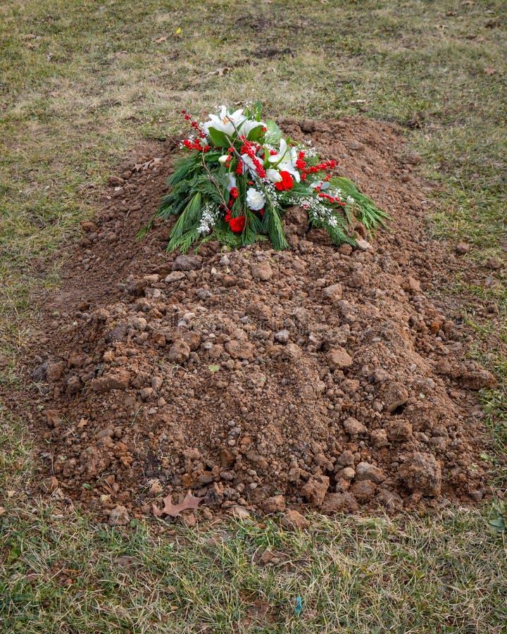 Nytt grävd grav med kyrkogårdblommor överst av jordning arkivfoton