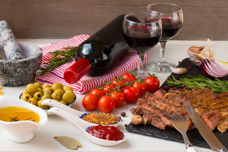 Nytt grillat kött Grillad nötköttentrecôtemedelstek på svart stenbräde, rött vin och två fulla vinexponeringsglas royaltyfri bild