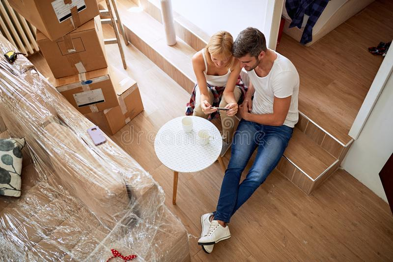 Nytt hem f?r parinflyttning Sitta på golv och koppla av, når att ha gjort ren och uppackning arkivfoton