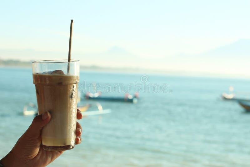 Nytt iskaffe mj?lkar med bl? strandbakgrund p? dagtid Ferielynne Ny drink i hand arkivbilder