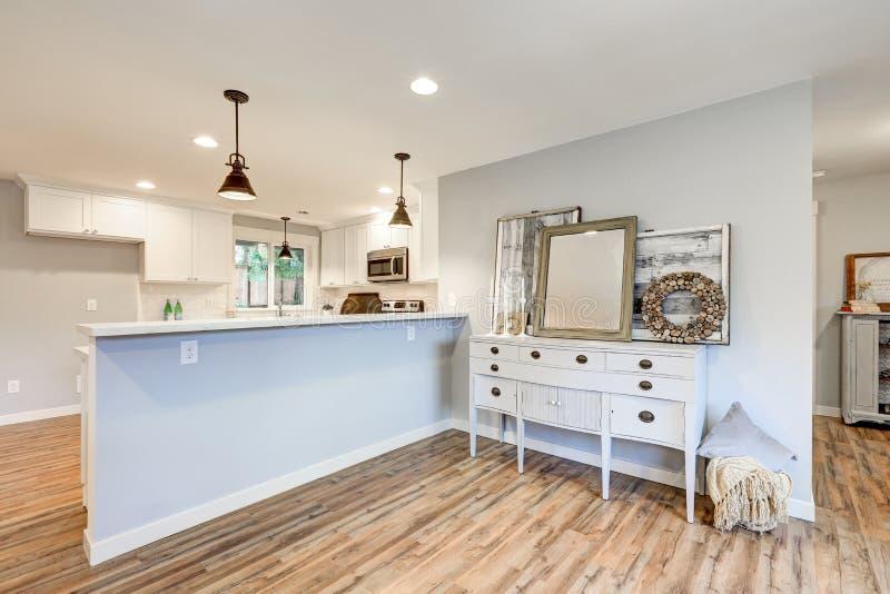 Nytt kök med den vita kabinetter, gångtunneltegelplattan och frukoststången fotografering för bildbyråer