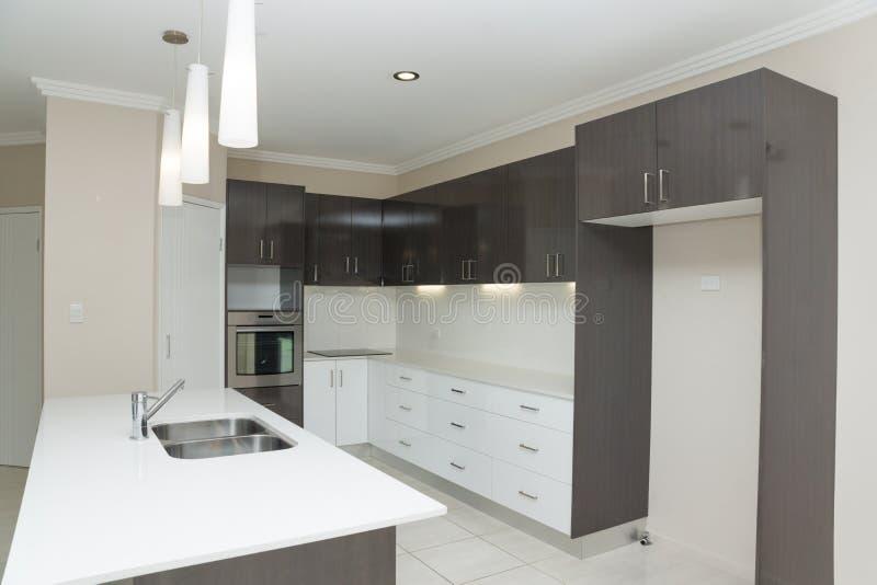 Nytt kök med granitbänken och det belade med tegel golvet fotografering för bildbyråer