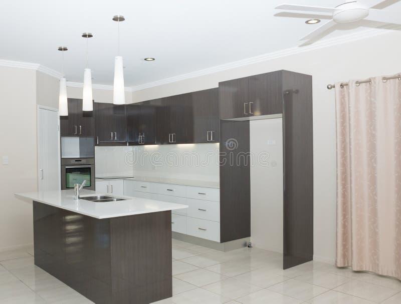 Nytt kök med granitbänken och det belade med tegel golvet royaltyfri foto