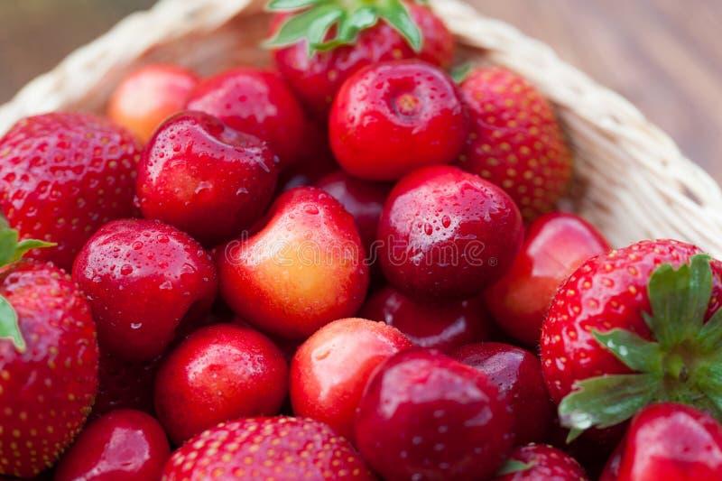 Nytt körsbärbär och röda mogna jordgubbar fotografering för bildbyråer