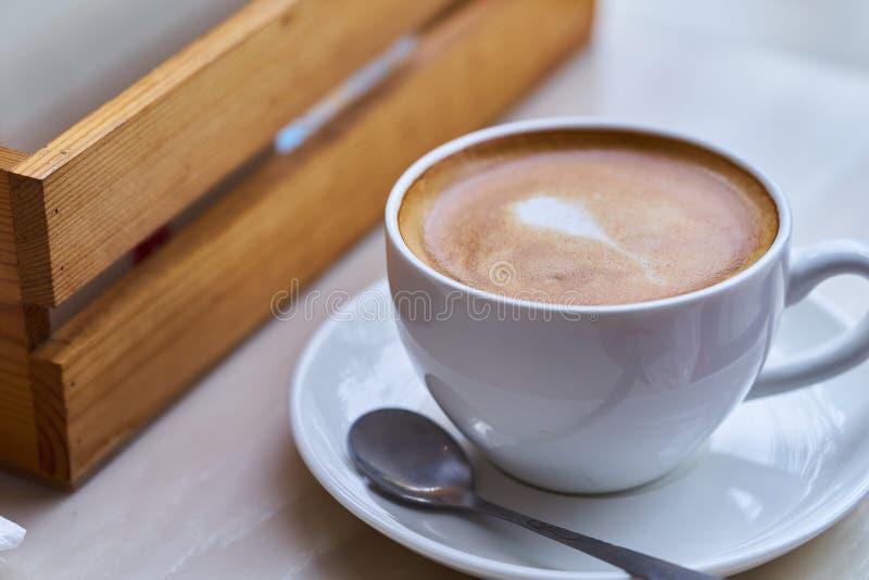 Nytt kaffe för varm Latte i den vita koppen på tabellen i kafé arkivbilder