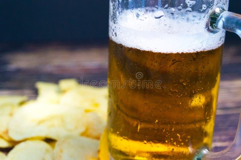 Nytt kallt öl i ett svettigt exponeringsglas på en suddig bakgrundsnärbild royaltyfri bild