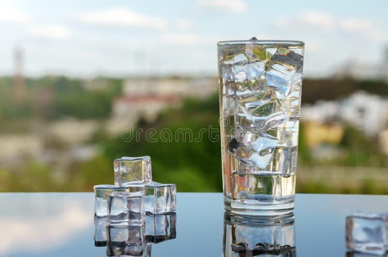 Nytt kallt vattenexponeringsglas med iskuber på landskapbakgrund fotografering för bildbyråer