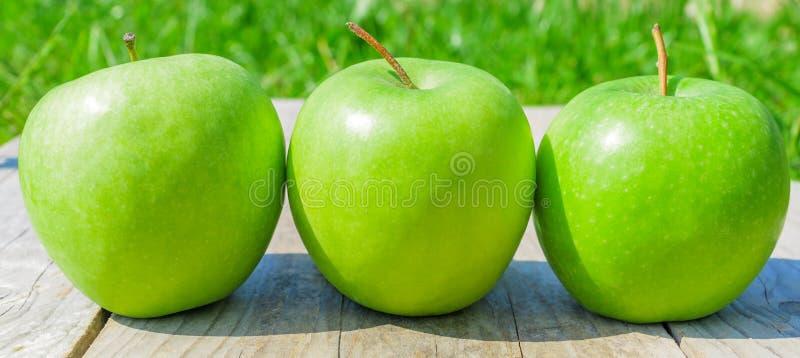 Nytt kantjusterat geen äpplen på trätabellen över grön bakgrund, baner royaltyfri fotografi